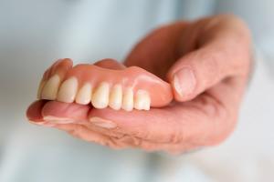 roka, kas tur zobu protēzes